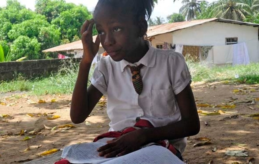 In this photo taken on Friday, May 8, 2015, Mercy Kennedy looks up as she does her homework after school at her home in Monrovia, Liberia. On the day Mercy Kennedy lost her mother to Ebola, it was hard to imagine a time Liberia would be free of one of the world's deadliest viruses. It had swept through the 9-year-old's neighborhood, killing people house by house. Now seven months later, Liberia on Saturday officially marked the end of the epidemic that claimed more than 4,700 lives here, and Mercy is thriving in the care of a family friend not far from where she used to live. (AP Photo/ Abbas Dulleh)