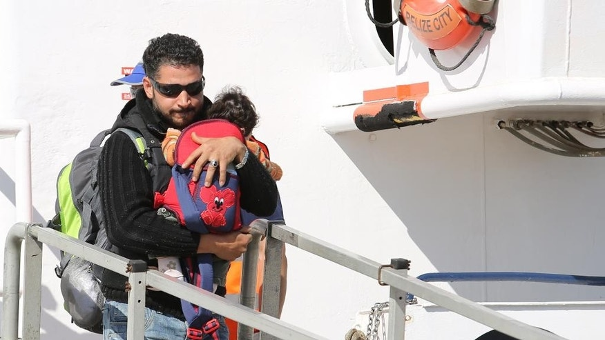 A migrant carries a baby ah he disembarks from the Migrant Offshore Aid Station vessel ' Phoenix ' in the harbor of Augusta, Sicily, Southern Italy, Saturday, May 9, 2015. European Union plans to introduce a quota system obliging countries to share the burden of settling refugees unraveled Friday as member nations began rejecting the scheme. (AP Photo/Francesco Malavolta)