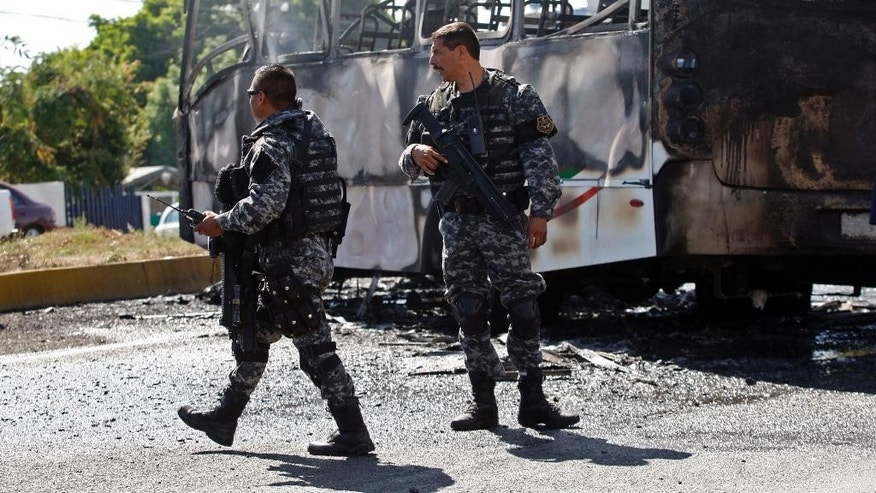 FILE - In this May 1, 2015 file photo, state police stand next to a charred passenger bus, that was extinguished by firefighters in Guadalajara, Mexico. Authorities in western Mexico asked residents to stay at home as they scrambled to extinguish burning vehicles that blocked roads in various parts of Guadalajara. Such blockades are a common cartel response to the arrest of important members or are used to foil police and military operations. (AP Photo, File)
