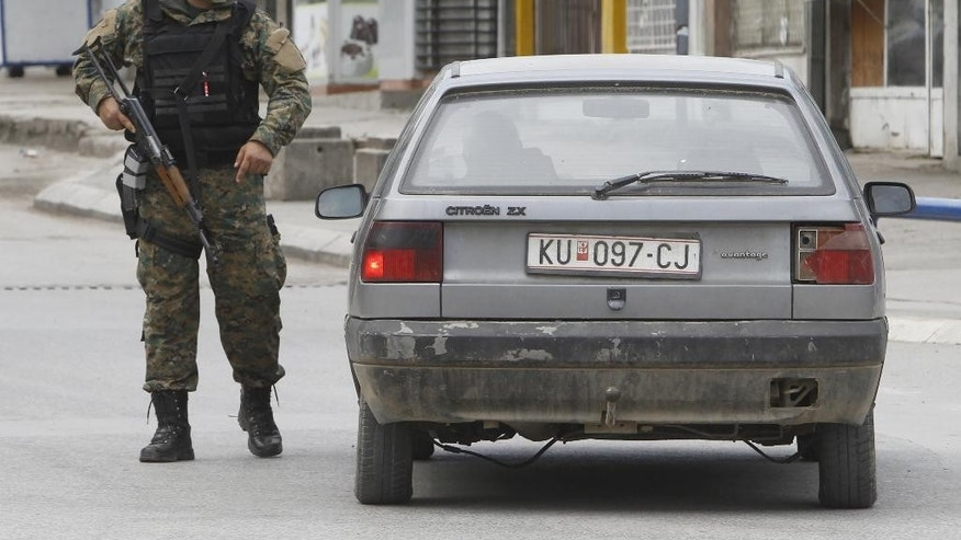 A police officer stops a vehicle near the area where a massive police action has been going on in northern Macedonian town of Kumanovo, on Saturday, May 9, 2015. Police clashed with an armed group in Kumanovo early Saturday authorities said. Macedonian state running agency MIA reported that four police officers were wounded in the shooting.  (AP Photo/Boris Grdanoski)