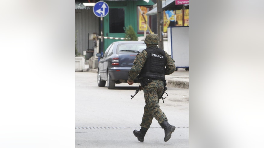 A police officer runs as shooting is heard near the area where a massive police action has been going on in northern Macedonian town of Kumanovo, on Saturday, May 9, 2015. Police clashed with an armed group in Kumanovo early Saturday authorities said. Macedonian state running agency MIA reported that four police officers were wounded in the shooting.  (AP Photo/Boris Grdanoski)