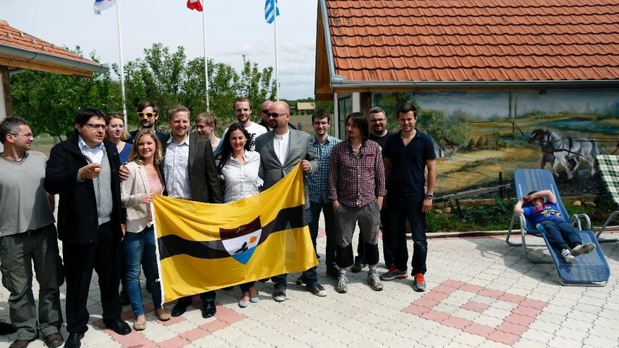 Vit Jedlicka, self-declared president of Liberland, fourth from left, poses with flag and supporters of the Liberland idea, in Backi Monostor, Serbia, Friday, May 1, 2015. The inauguration of world's new mini-state in the war-torn Balkans may sound as an elaborate joke by international organizers, but Croats and Serbs aren't laughing. The so-called Free Republic of Liberland, a 7-square-kilometer swampy patch of isolated land on the banks of the Danube river border between Serbia and Croatia _ which fought a war in the 1990s _ has been blocked by police in both states. (AP Photo/Darko Vojinovic)