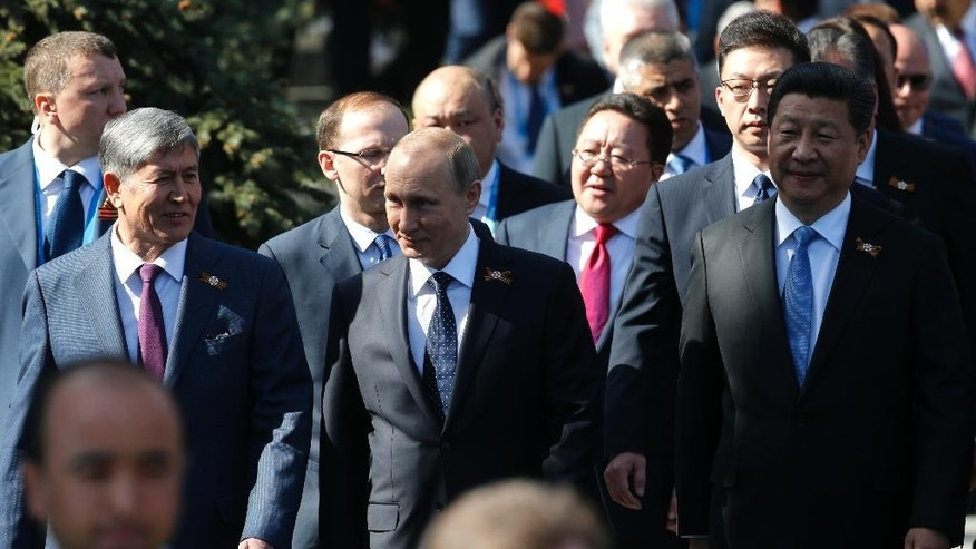 From left:  Kyrgyz President Almazbek Atambayev, Russian President Vladimir Putin, Chinese President Xi Jinping walk before the Victory Parade marking the 70th anniversary of the defeat of the Nazis in World War II, in Red Square, Moscow, Russia, Saturday, May 9, 2015. (AP Photo/Alexander Zemlianichenko, Pool)