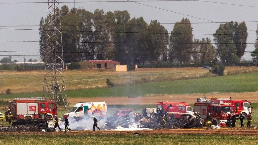 Emergency services personnel work in the area after a plane crash near the Seville airport, in Spain, Saturday, May 9, 2015. A military transport plane crashed near southwestern Seville airport Saturday, killing its crew, Spain's prime minister said. It is unclear if any others were injured. Mariano Rajoy said up to 10 crew members were aboard the brand new Airbus A400M aircraft that was undergoing flight trials at the airport. (AP Photo/Miguel Angel Morenatti)