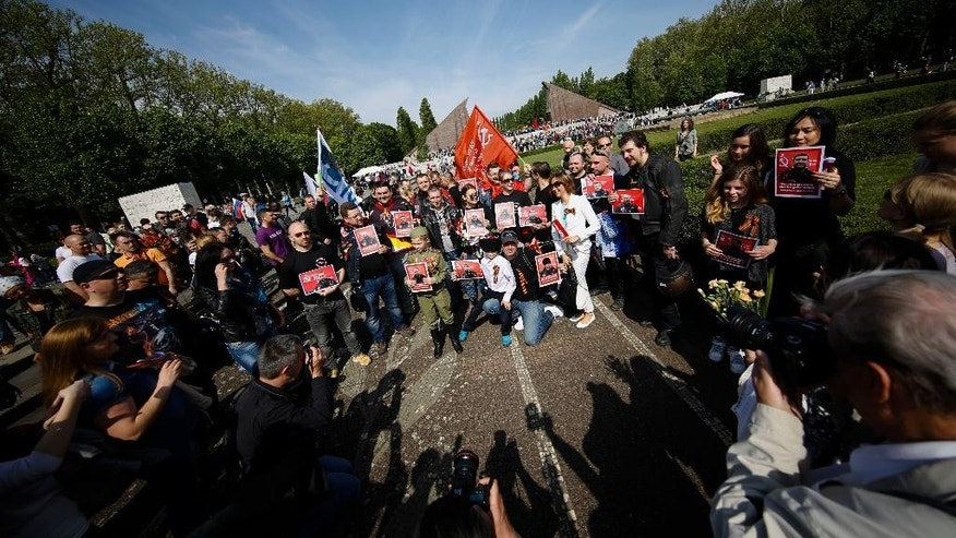 Sympathizers of the Russian motorcycle club Night Wolves show posters of members of the motorcycle club with the sentence: 'They have managed to come to Berlin' as they pose for photographers and media at the Russian War Memorial to commemorate the end of World War II 70 years ago, at the district Treptow in Berlin, Germany, Saturday, May 9, 2015.  (AP Photo/Markus Schreiber)