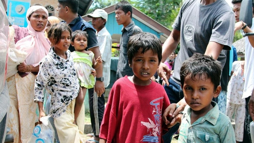 Ethnic Rohingya children whose boats were washed ashore wait to be evacuated to a temporary shelter in Seunuddon, Aceh province, Indonesia, Sunday, May 10, 2015. Boats carrying about 500 members of Myanmar's long-persecuted Rohingya Muslim community washed to shore in western Indonesia on Sunday, with some of the people in need of medical attention, a migration official and a human rights advocate said. (AP Photo/S. Yulinnas)