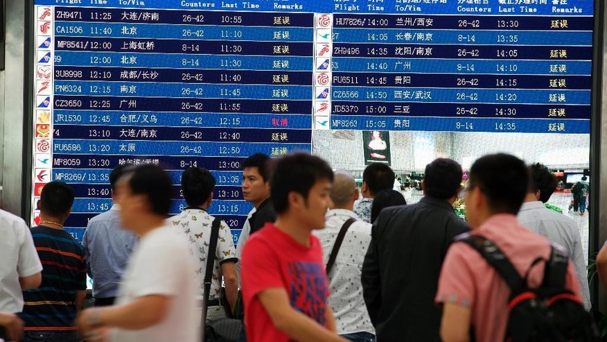 In this photo released by China's Xinhua News Agency, passengers check flight information at Changle International Airport in Fuzhou, capital of southeast China's Fujian Province, Sunday, May 10, 2015.  A Chinese plane veered off a runway upon landing in the southeastern city of Fuzhou on Sunday, the domestic carrier Joyair said. (Jiang Kehong/Xinhua via AP) NO SALES