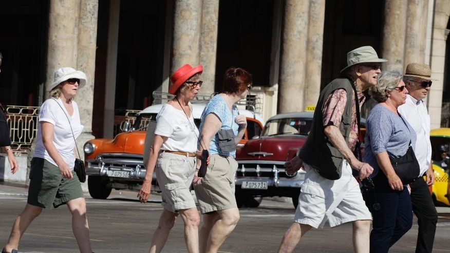 March 13, 2015: In this file photo, tourists cross traffic lights in Havana, Cuba. Tourists in shorts and sandals aren't the only foreigners flooding Havana these days.