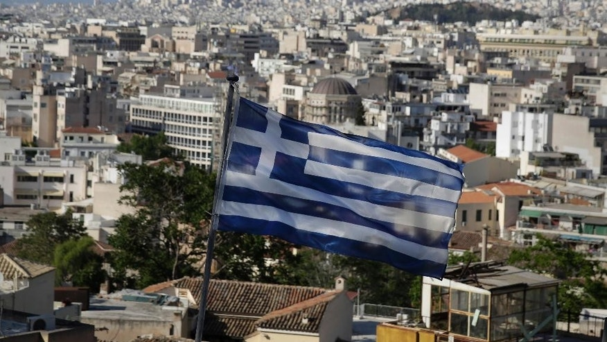 A Greek national flag flies in the city of Athens, Friday, May 8, 2015. Greece's prime minister Alexis Tsipras said Friday he is optimistic his cash-strapped country will soon reach an agreement with its international creditors, averting a potential default. (AP Photo/Petros Giannakouris)