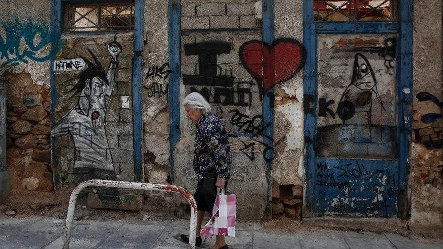A woman walks past an abandoned house in a neighborhood in Athens, Greece, Friday, May 8, 2015. Greece's prime minister said Friday he is optimistic his cash-strapped country will soon reach an agreement with its international creditors, so averting a potential default. (AP Photo/Yorgos Karahalis)