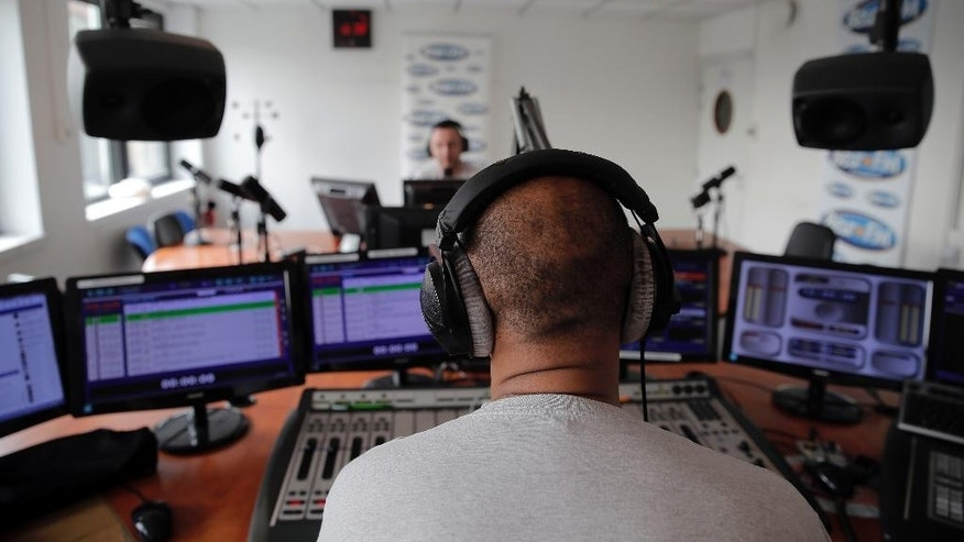 "In this  Friday, April 17, 2015 photo Dj Sem, background, answers radio host Tarik at Beur FM radio in Paris, France.  It's called ""Beur FM"" - after a slang term for Arab people - and has become the voice of France's Islamic community in the wake of the Charlie Hebdo attacks. Since terror struck the heart of Paris in January, Beur FM has become a staple for listeners of all walks of life who are hungry for answers about the violence - and how to reconcile alienated immigrants with mainstream society. (AP Photo/Christophe Ena)"