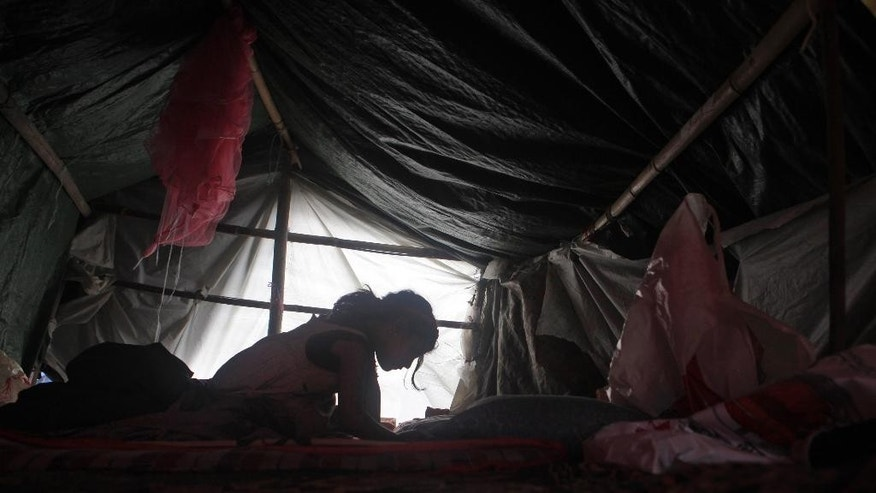 A Nepalese girl studies inside a makeshift tent in Kathmandu, Nepal, Saturday, May 9, 2015. The international response has been slow to an appeal for emergency funds to help the millions of people hit by last month's earthquake in Nepal, a U.N. official said Friday. Jamie McGoldrick, the U.N.'s chief official in Nepal, said the agency had received $22 million so far against an appeal last week for $415 million to support relief efforts for the first three months in the Himalayan nation. (AP Photo/Niranjan Shrestha)
