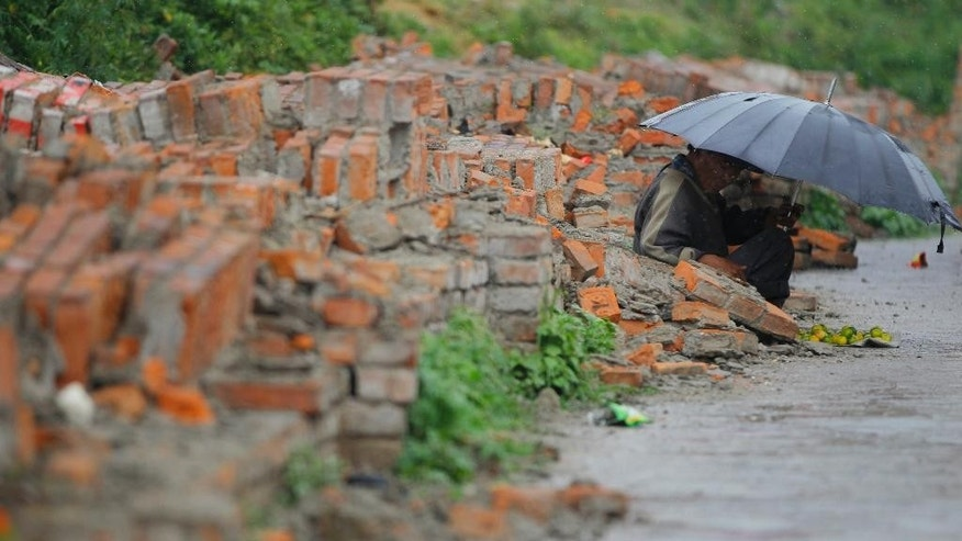 A Nepalese street vendor waits for customers in front of a broken wall in Kathmandu, Nepal, Saturday, May 9, 2015. The international response has been slow to an appeal for emergency funds to help the millions of people hit by last month's earthquake in Nepal, a U.N. official said Friday. Jamie McGoldrick, the U.N.'s chief official in Nepal, said the agency had received $22 million so far against an appeal last week for $415 million to support relief efforts for the first three months in the Himalayan nation. (AP Photo/Niranjan Shrestha)