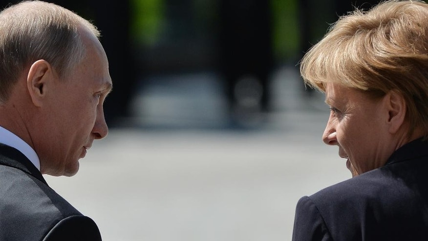 Russian President Vladimir Putin, left, and German Chancellor Angela Merkel walk away after a wreath-laying ceremony at the Tomb of the Unknown Soldier, marking the 70th anniversary of the defeat of the Nazis in World War II, in Moscow, Russia, Sunday, May 10, 2015. (Host photo agency/RIA Novosti Pool Photo via AP)