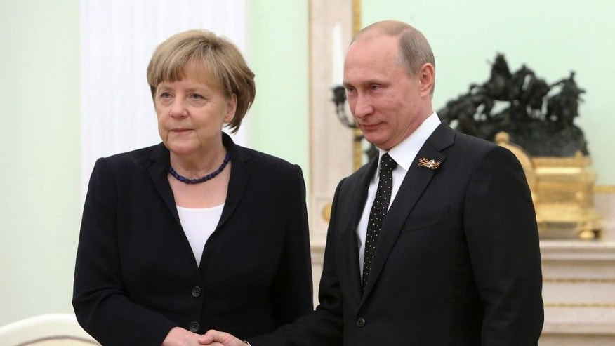 German Chancellor Angela Merkel, left, and Russian President Vladimir Putin shake hands during their meeting in the Kremlin in Moscow, Russia, Sunday, May 10, 2015. Angela Merkel attended a wreath-laying ceremony at the Tomb of the Unknown Soldier, marking the 70th anniversary of the defeat of the Nazis in World War II, in Moscow. (Sergei Karpukhin/Pool Photo via AP)