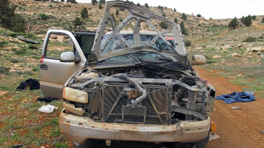 This Saturday, May 9, 2015 photo shows a damaged SUV left behind by members of the Nusra Front, al-Qaida's branch in Syria, in a position captured by Lebanon's Hezbollah fighters in the fields of the Syrian border town of Assal al-Ward. Hezbollah fighters have been spearheading an attack along with President Bashar Assad's troops against Sunni insurgents in Syria's rugged mountainous region of Qalamoun. On Saturday, Hezbollah fighters showed several local journalists and an Associated Press team positions they recently captured in Qalamoun. (AP Photo/Bassem Mroue)
