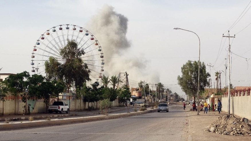 In this Saturday, May 9, 2015 photo, smoke rises after an airstrike by the U.S.-led coalition on Islamic State group positions in an eastern neighborhood of Ramadi, the capital of Anbar province, 70 miles (115 kilometers) west of Baghdad, Iraq. Iraqi authorities on Friday signed up the first batch of 1,000 recruits for a new Sunni militia to help its security forces take back the western Anbar province from the Islamic State group, after years of reluctance to arm and train the tribal fighters. (AP Photo)