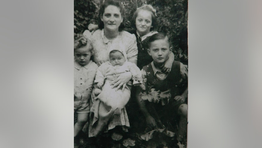 This photograph, taken in 1947 in Dzierzoniow, Poland, shows Moshe Tirosh as a boy with his mother and siblings.