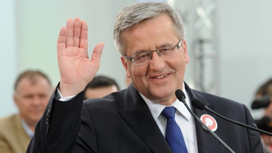 Polish President Bronislaw Komorowski greets supporters during a meeting ending his campaign ahead of a Sunday's presidential election, Warsaw, Poland, Friday, May 8, 2015. Komorowski, who his running for his second term and right wing candidate Andrzej Duda are the main contenders in the upcoming vote. (AP Photo/Alik Keplicz)