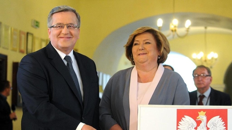 Polish President Bronislaw Komorowski casts his ballot, as his wife Anna watches in the first round of the presidential election in Warsaw, Poland, Sunday, May 10, 2015. The Poles are voting for president in nationwide balloting that is expected to see incumbent Komorowski, re-elected, but not in the first voting round. (AP Photo/Alik Keplicz)
