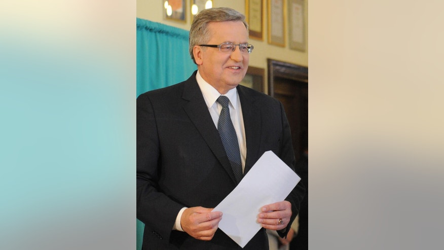Polish President Bronislaw Komorowski holds his ballot before voting in the first round of the presidential election in Warsaw, Poland, Sunday, May 10, 2015. The Poles are voting for president in nationwide balloting that is expected to see incumbent Komorowski, re-elected, but not in the first voting round. (AP Photo/Alik Keplicz)