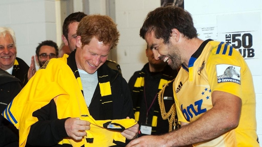Hurricanes captain Conrad Smith, right, presents Britain's Prince Harry with a personalized onesie for his brother Prince William's daughter, Princess Charlotte in the Hurricanes changing rooms after the Super Rugby against the Sharks at Westpac Stadium in Wellington, New Zealand, Saturday, May 9, 2015. (Dave Lintott/Pool Photo via AP)