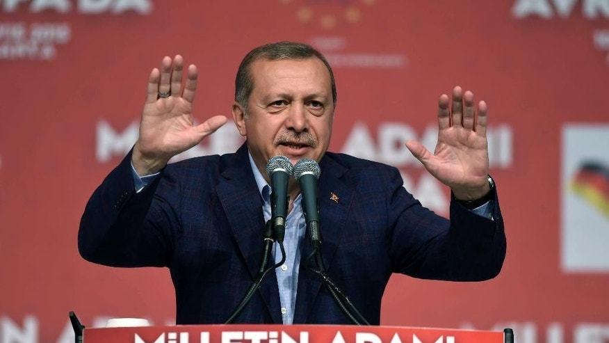 Turkish President Recep Tayyip Erdogan delivers a speech in an exhibition hall in Karlsruhe, Germany, Sunday, May 10, 2015. Erdogan has urged compatriots during his appearance to preserve their homeland's values and language and to vote ahead of upcoming Turkish elections. (Ulli Deck/dpa via AP)