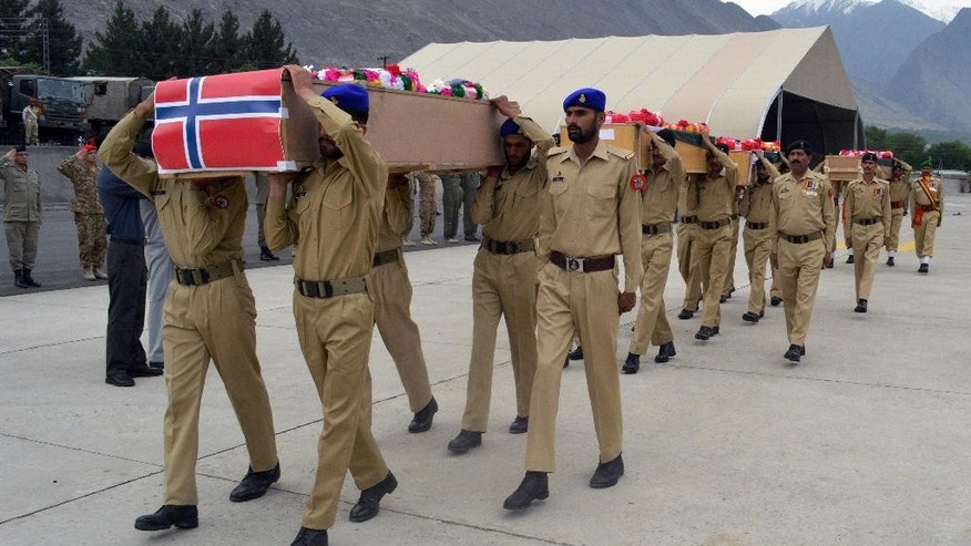 Pakistani soldiers carry the caskets of victims of a helicopter crash to a military plane prior to their transport to Islamabad, at the small domestic airport of Gilgit, in the Gilgit-Baltistan region of Pakistan, Saturday, May 9, 2015.  The helicopter, transporting dignitaries to a ceremony at a ski resort, crashed and caught fire as it was landing on Friday killing seven people including ambassadors from the Philippines and Norway and the wives of the ambassadors from Malaysia and Indonesia. (AP Photo/M. Hussain)