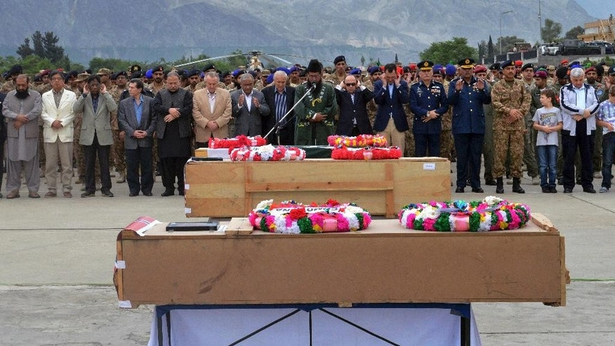Pakistani military officials and others offer prayers for victims of a helicopter crash prior to their transport to Islamabad, at the Gilgit airport, in the Gilgit-Baltistan region of Pakistan, Saturday, May 9, 2015.  The helicopter, transporting dignitaries to a ceremony at a ski resort, crashed and caught fire as it was landing on Friday killing seven people including ambassadors from the Philippines and Norway and the wives of the ambassadors from Malaysia and Indonesia. (AP Photo/M. Hussain)