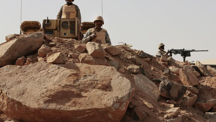 "FILE - In this Tuesday, April 21, 2015 file photo, Saudi soldiers stand on top of armor vehicles, on the border with Yemen at a military point in Najran, Saudi Arabia.  A Saudi-owned news channel, al-Hadath, aired live footage Monday, May 11, 2015 of tanks and armored personnel carriers loaded onto giant trucks, saying they were part of a ""strike force"" deploying to the kingdom's border with Yemen. There have been no signs to suggest that a ground offensive was imminent, although the coalition has not ruled one out.(AP Photo/Hasan Jamali, File)"