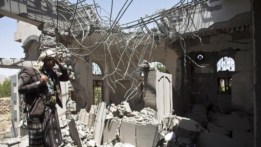 A Shiite fighter known as a Houthi inspects his house destroyed by a Saudi-led airstrike in Sanaa, Yemen, Monday, May 11, 2015. Shiite rebels in Yemen claimed Monday to have shot down a Moroccan F-16 fighter jet taking part in a Saudi-led coalition targeting them and their allies, just a day before a five-day humanitarian cease-fire was set to begin. (AP Photo/Hani Mohammed)