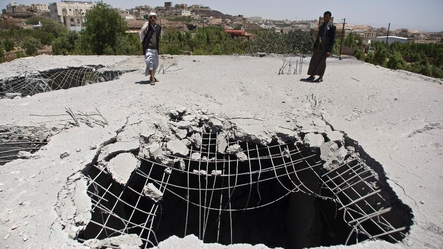 Shiite rebels known as Houthis inspect a house destroyed by a Saudi-led airstrike in Sanaa, Yemen, Monday, May 11, 2015. Shiite rebels in Yemen claimed Monday to have shot down a Moroccan F-16 fighter jet taking part in a Saudi-led coalition targeting them and their allies, just a day before a five-day humanitarian cease-fire was set to begin. (AP Photo/Hani Mohammed)