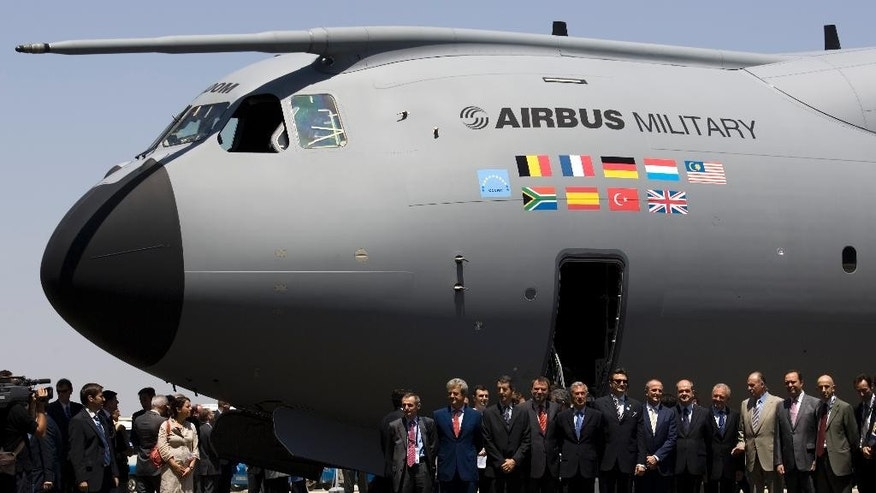 FILE - In this June 26, 2008 file photo, Spanish King Juan Carlos, fourth from right, poses with other officials in front of the new military Airbus A400M in Seville, Spain. Investors pushed Airbus shares down Monday May 11, 2015 on Paris' stock exchange after an Airbus military transport plane undergoing final flight testing in Spain crashed, killing four aboard and injuring two. Airbus shares were down 4.3 percent to 60.67 euros ($67.88) as authorities investigated what caused the A400M to crash into a farm field Saturday after taking off from Seville, where the planes are assembled.(AP Photo/Victor R. Caivano, File)