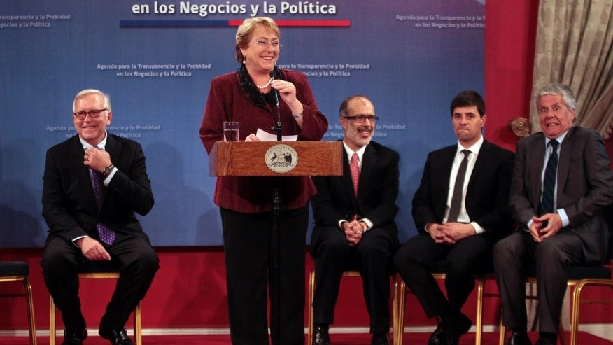 Chile's President Michelle Bachelet speaks at a ceremony announcing new Cabinet members at the presidential palace La Moneda, in Santiago, Chile, Monday, May 11,  2015.  Pictured in the background are Interior Minister Jorge Burgos, from left, Finance Minister Rodrigo Valdes, Government Spokesman Marcelo Diaz, and Education Minister Nicolas Eyzaguirre. (AP Photo/Luis Hidalgo)