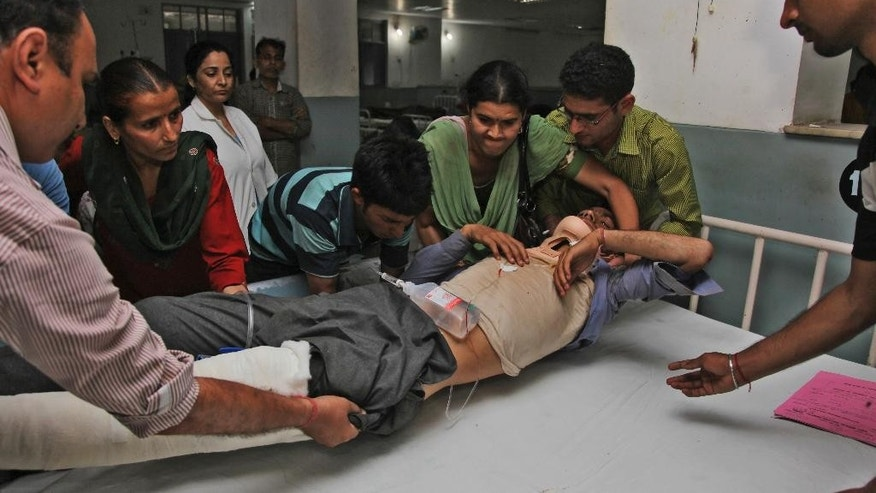 Rakesh Kumar, who was injured in a bus accident, is brought for treatment at the government medical college hospital in Jammu, India, Monday, May 11, 2015. A crowded bus veered off a rocky village road and fell into a deep gorge on Monday, killing more than twenty people in the Indian-controlled portion of the disputed Himalayan region of Kashmir, police said. (AP Photo/Channi Anand)
