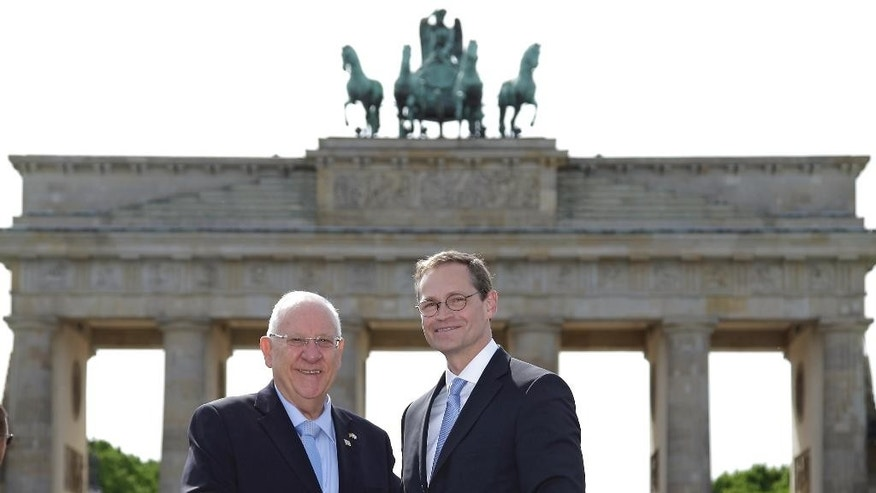 Mayor of Berlin Michael Mueller, right, and President of Israel Reuven Rivlin, left, shake hands as they pose in front of the Brandenburg Gate in Berlin, Germany, Monday, May 11, 2015. (AP Photo/Michael Sohn)