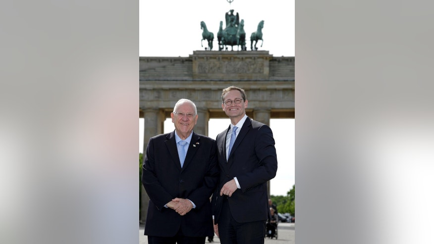 Mayor of Berlin Michael Mueller, right, and President of Israel Reuven Rivlin, left, smile as they pose in front of the Brandenburg Gate in Berlin, Germany, Monday, May 11, 2015. (AP Photo/Michael Sohn)