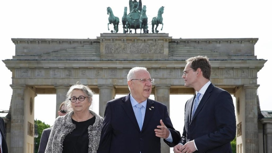 Mayor of Berlin Michael Mueller, right, the President of Israel Reuven Rivlin, center, and his wife Nechama Rivlin, left, talk as they pose in front of the Brandenburg Gate in Berlin, Germany, Monday, May 11, 2015. (AP Photo/Michael Sohn)