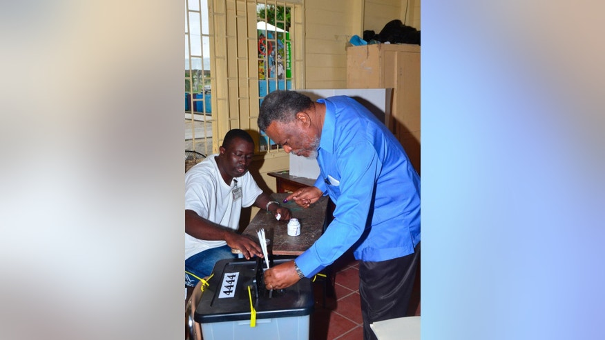 A poll worker helps Guyana Prime Minister Samuel Hinds cast his ballot in the general elections, in Georgetown, Guyana, Monday, May 11, 2015. A party in power for over two decades in Guyana faced off in general elections Monday against a new coalition of opposition parties that seeks to challenge a tradition of racial politics and accuses the government of mismanagement and corruption. (AP Photo/Adrian Narine)