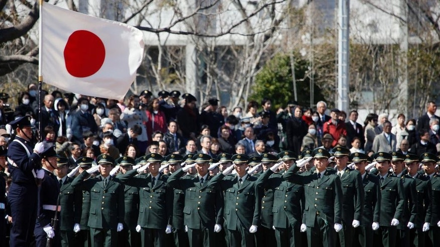 FILE - In this March 22, 2014 file photo, students of the National Defense Academy salute the national flag during a military parade to celebrate their senior students' graduation in Yokosuka, near Tokyo. Japanese Prime Minister Shinzo Abe is moving ahead this week with legislation that would boost the military's international role in a significant shift of its pacifist policies. His ruling coalition is set to reach formal agreement Monday, May 11, 2015 on a package of bills that would loosen restrictions imposed on the military by the U.S. occupation after World War II.  (AP Photo/Koji Sasahara, File)