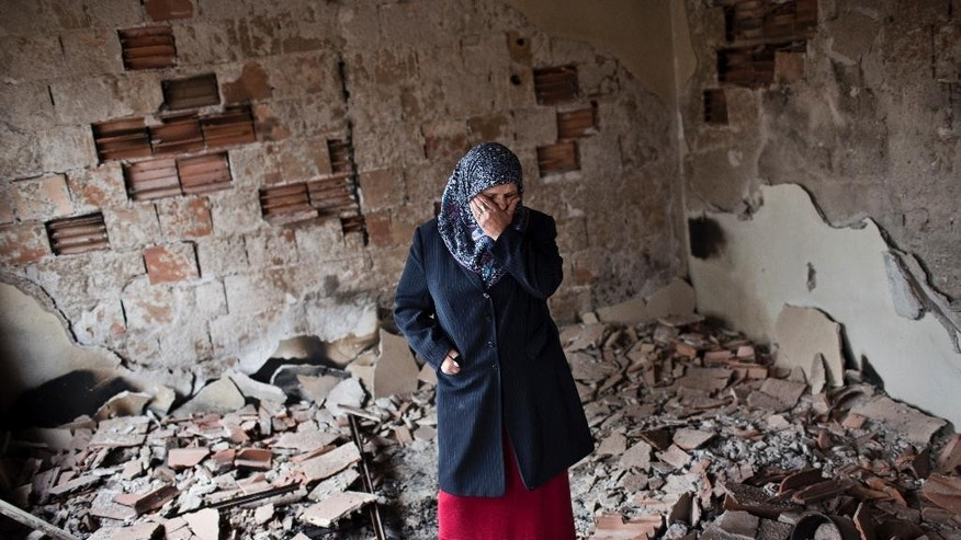 Habibe Biyali stands inside a room in her house heavily damaged by fighting in Kumanovo, Macedonia, Monday, May 11, 2015.  Residents are returning to their homes in a northern Macedonian town where a fierce weekend battle between special police units and alleged ethnic Albanian militants left 22 dead and at least 37 injured. (AP Photo/Marko Drobnjakovic)