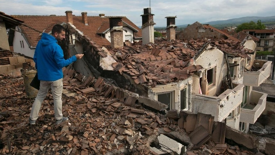 Resident take pictures of the destruction in a neighborhood wHere a battle took place over the weekend involving the police and an armed group, in northern Macedonian town of Kumanovo, early Monday, May 11, 2015. (AP Photo/Visar Kryeziu)