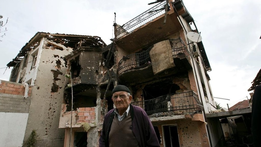 A resident visits the neighborhood where a battle took place over the weekend involving the police and an armed group, in northern Macedonian town of Kumanovo, early Monday, May 11, 2015. (AP Photo/Visar Kryeziu)