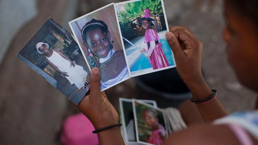 "In this May 8, 2015 photo, a relative of Anne-Marie Saintou shows Saintou's daughter in pictures sent to Haiti from the girl's adopted family in France, as she holds them inside Saintou's home in Arcahaie, Haiti. Saintou placed her daughter up for adoption 12 years ago when she was 3-year-old, with the understanding that her daughter would get an education and come back. After she was adopted by a family in France, Saintou received one letter and photos in the mail but then lost contact. ""I never heard from her again,"" Saintou said. (AP Photo/Dieu Nalio Chery)"
