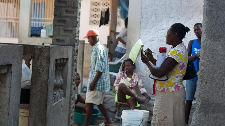 In this May 8, 2015 photo, Anne-Marie Saintou collects people's contact information and a count of how many children they have as she shares the location and contacts of the Mercy & Sharing residential center, where she volunteers, which runs residential centers and schools for disabled and abandoned children, in the seaside community of Luly in Arcahaie, Haiti. Saintou warns people not to make the same mistake she did. She lost contact with her daughter Mikerline, who was adopted by a French family 12 years ago, thinking her three-year-old would return after getting an education. (AP Photo/Dieu Nalio Chery)