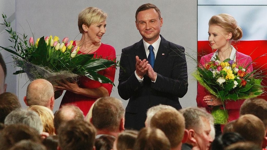 Main opposition candidate Andrzej Duda, with wife Agata, left, and daughter Kinga, right, greets supporters during his election night, as first exit polls show he won the first round of the presidential balloting, in Warsaw, Poland, Sunday, May 10, 2015.(AP Photo/Czarek Sokolowski)