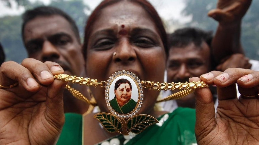 A member of All India Anna Dravida Munnetra Kazhagam (AIADMK) displays a locket with a portrait of party supremo and former Tamil Nadu state chief minister Jayaram Jayalalitha as she celebrates a court verdict in Chennai, India, Monday, May 11, 2015. An appeals court in southern India acquitted powerful regional politician Jayalalitha of corruption charges Monday, clearing the way for her to return to public office. Jayalalitha was forced last year to step down as the highest elected official in the southern state of Tamil Nadu, after a Bangalore court in September convicted her of possessing wealth disproportionate to her income and sentenced her to four years in prison. (AP Photo/Arun Sankar K.)