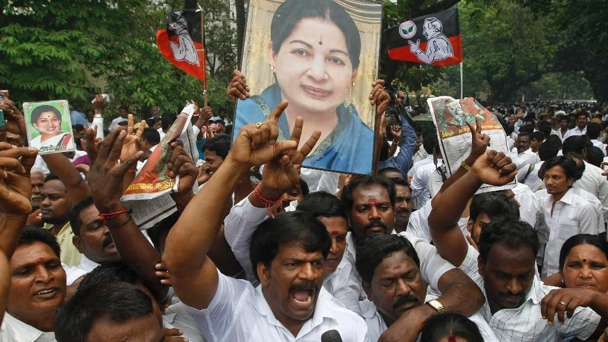 Members of All India Anna Dravida Munnetra Kazhagam (AIADMK) hold a portrait of party supremo and former Tamil Nadu state chief minister Jayaram Jayalalitha as they celebrate a court verdict in Chennai, India, Monday, May 11, 2015. An appeals court in southern India acquitted powerful regional politician Jayalalitha of corruption charges Monday, clearing the way for her to return to public office. Jayalalitha was forced last year to step down as the highest elected official in the southern state of Tamil Nadu, after a Bangalore court in September convicted her of possessing wealth disproportionate to her income and sentenced her to four years in prison. (AP Photo/Arun Sankar K.)