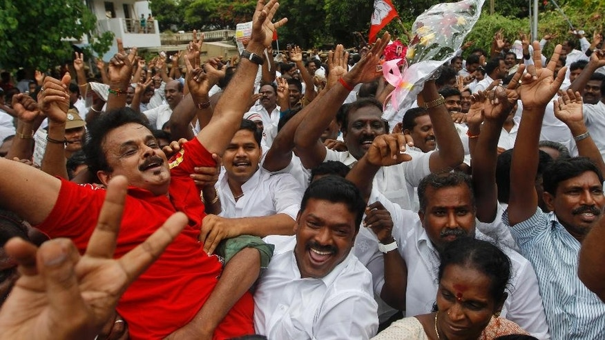 Supporters of Jayaram Jayalalitha cheer after an appeals court in southern India acquitted her of corruption charges in Chennai, India, Monday, May 11, 2015. Jayalalitha was forced last year to step down as the highest elected official in the southern state of Tamil Nadu, after a Bangalore court in September convicted her of possessing wealth disproportionate to her income and sentenced her to four years in prison. (AP Photo/Arun Sankar K)