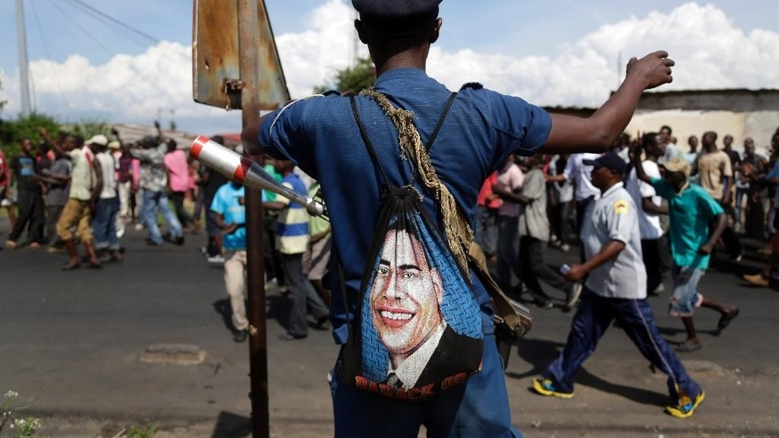 A police officer with a bag depicted the image of US President Barack Obama, stands on patrol as protesters march through the Musaga district of Bujumbura, in Burundi, Monday, May 11, 2015.  Police and army negotiated with over 2000 protesters to allow delivery trucks to enter the city. One person was killed in a clash with Burundi's police on Sunday in demonstrations in the capital, Bujumbura, as the government ordered a ban on any further street protests over President Pierre Nkurunziza's bid for a third term in power. (AP Photo/Jerome Delay)